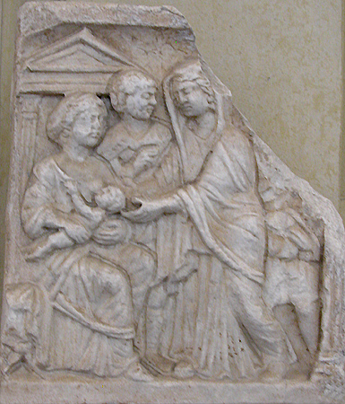 ... seated while nursing her infant before a temple; a male (her husband?